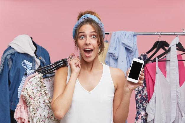 Opgewonden vrouw op zoek met grote verbazing, met hangers met kleren terwijl staande in de garderobe, demonstrerende mobiele telefoon met een leeg scherm. mensen, winkelen, technologie concept Gratis Foto