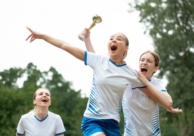 Opgewonden vrouwen met beker voor winnaars Gratis Foto