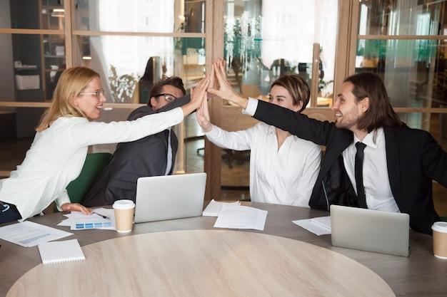 Opgewonden werk team geven hoge vijf vieren gedeelde prestatie Gratis Foto