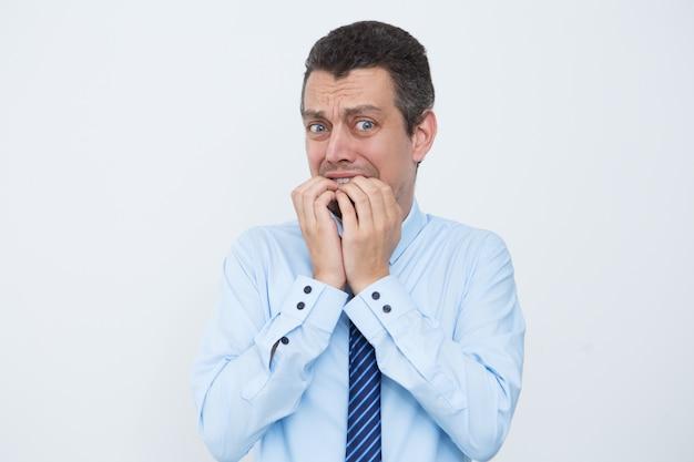 Opgewonden zakenman kauwen vingernagels Gratis Foto