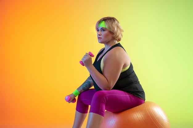 Opleiding van het jonge kaukasische plus grootte vrouwelijke model op oranje achtergrond met kleurovergang in neonlicht. trainingsoefeningen doen met de gewichten. concept van sport, gezonde levensstijl, positief lichaam, gelijkheid. Gratis Foto