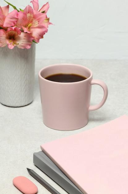 Opmerking boeken, potlood, koffiekopje, boeket bloemen op stenen tafel Premium Foto