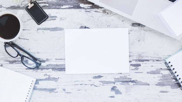 Opmerking en laptop in de buurt van briefpapier en koffiekopje Gratis Foto