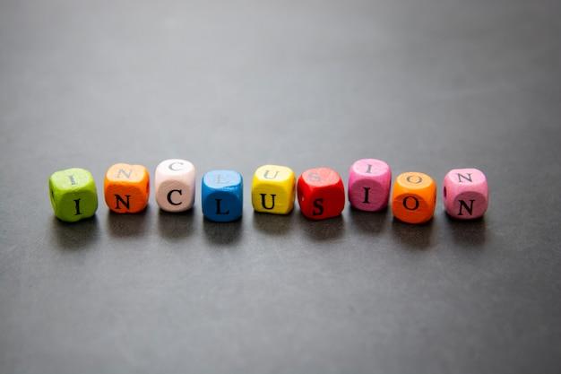 Opnametekst van multi gekleurde kubussen op donkere achtergrond. inclusief sociaal concept. Premium Foto