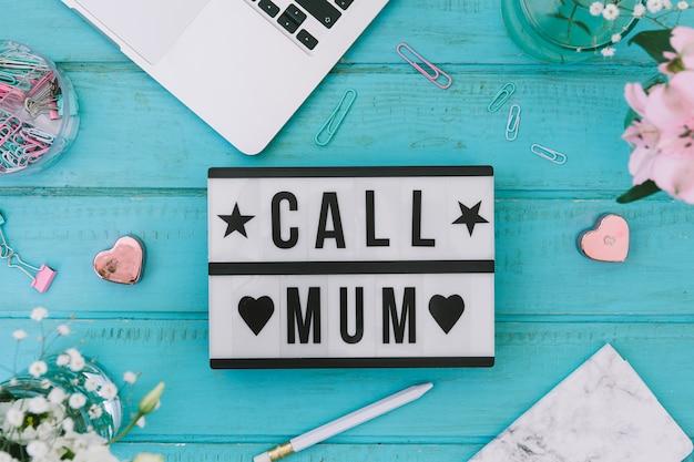 Oproep mama inscriptie met bloemen en laptop Gratis Foto