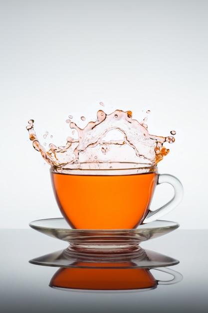 Opspattend kopje thee Premium Foto