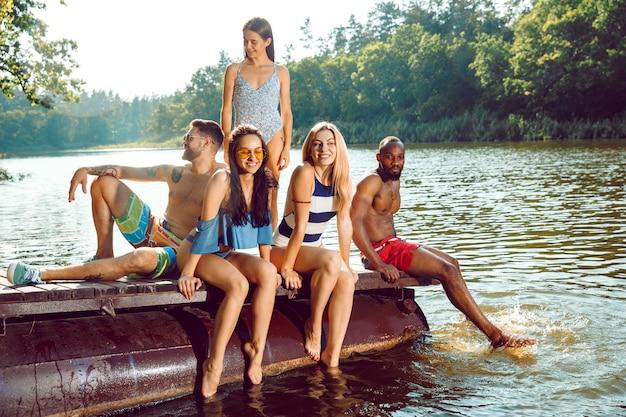 Opspattend water en lachend op de pier op de rivier Gratis Foto