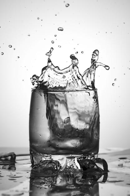Opspattend water. glas ijswater. Premium Foto