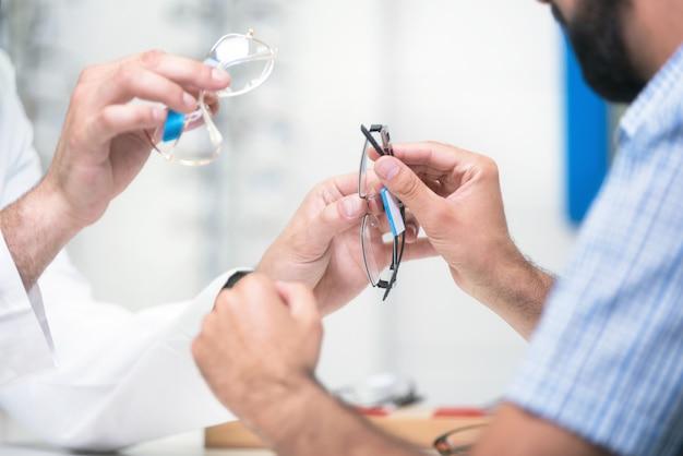 Opticien die glazen aanbieden aan klant voor het testen en het proberen Premium Foto