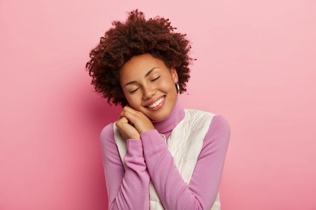 Optimistisch tienermeisje met natuurlijk krullend haar, kantelt hoofd en glimlacht vreugdevol, leunt op handen, houdt de ogen dicht, draagt comfortabele kleding, staat in schattige pose. Gratis Foto