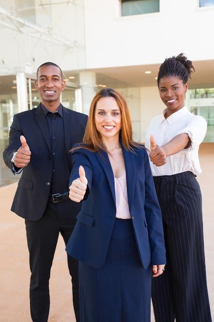 Optimistische jonge interracial zakenmensen die duim-omhoog tonen Gratis Foto