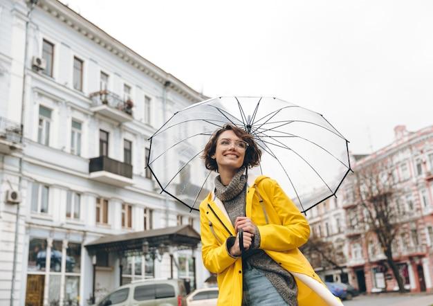 Optimistische vrouw in gele regenjas en glazen die pret hebben terwijl het lopen door stad onder grote transparante paraplu tijdens koude regenachtige dag Gratis Foto
