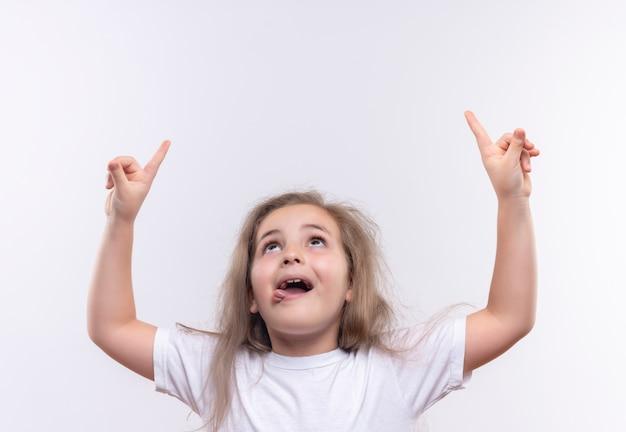 Opzoeken klein schoolmeisje draagt witte t-shirt wijst naar boven op afgelegen witte achtergrond Gratis Foto