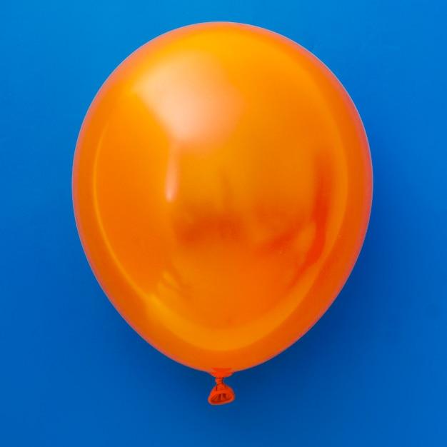 Oranje ballon op blauwe achtergrond Gratis Foto