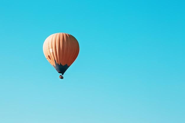 Oranje ballon stijgt tegen de blauwe hemel Premium Foto