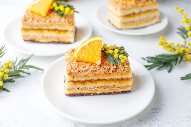 Oranje cake versierd met verse stukjes sinaasappel en mimosa bloemen op licht Gratis Foto