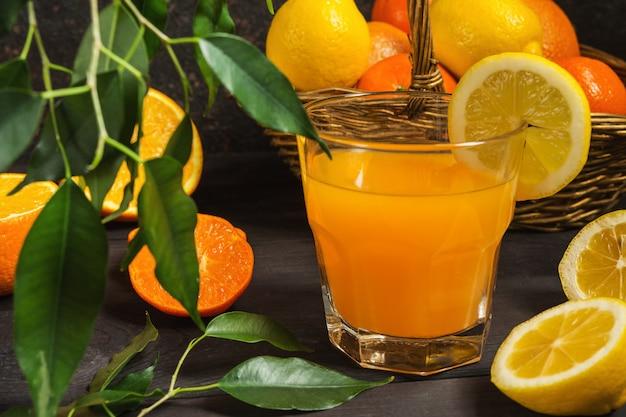 Oranje citroencitrusvruchten in een mand en een sap op een donkere achtergrond Premium Foto