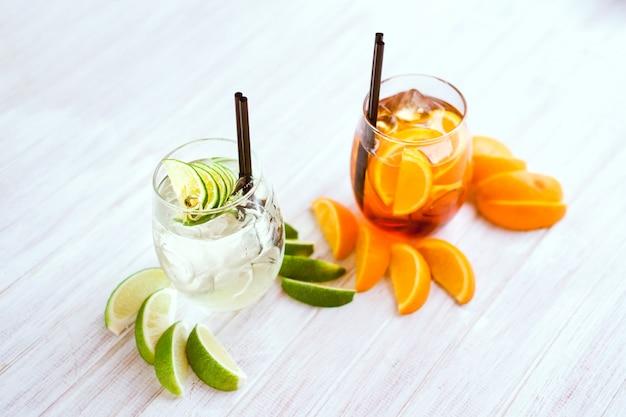 Oranje cocktail en ijsblokjes op witte achtergrond. Premium Foto