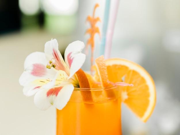 Oranje cocktail met fruit versierd met orchidee Gratis Foto