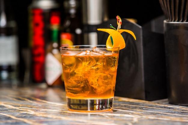 Oranje cocktail shot gegarneerd met sinaasappelschil Gratis Foto