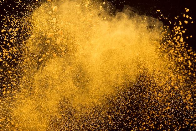 Oranje explosie van kosmetisch poeder op donkere achtergrond Gratis Foto