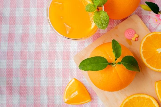 Oranje fruit en glas koud jus d'orange op roze tafelkleed. Premium Foto