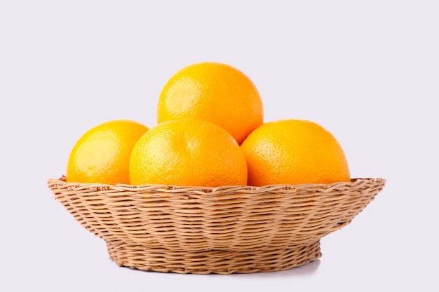 Oranje fruit in mand op een witte achtergrond Premium Foto