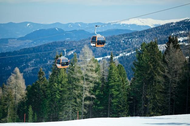 Oranje gondelcabines van kabelbaanlift op van de winter sneeuwbergen mooi landschap als achtergrond Premium Foto