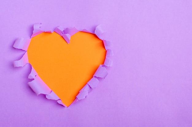 Oranje hartvormig gat door paars papier Premium Foto