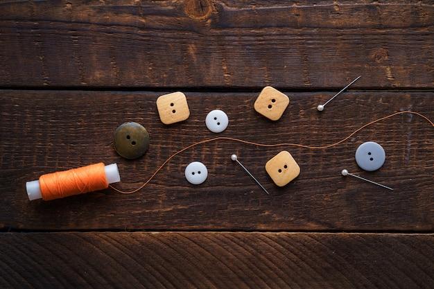 Oranje klos garen, spelden en knopen voor het naaien op een houten bruine ondergrond Premium Foto