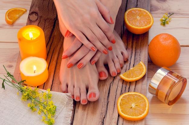 Oranje manicure rond sinaasappelen en kaarsen Premium Foto