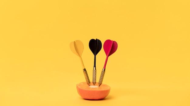 Oranje met darten op bureau Premium Foto