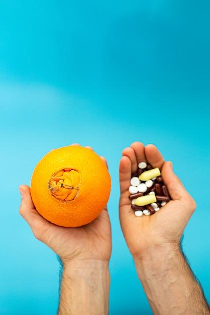 Oranje met een grote navel, pillen in handen op een blauwe achtergrond. aambei medicamenteuze behandeling concept. Premium Foto
