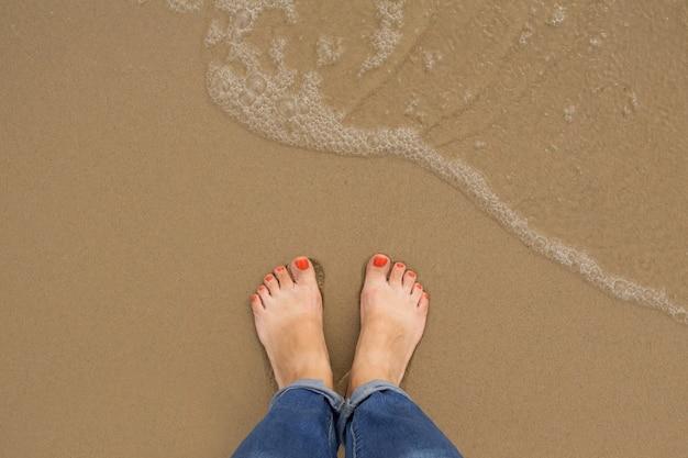Oranje nagel-pedicure voeten van vrouw op zomerzandstrand Premium Foto