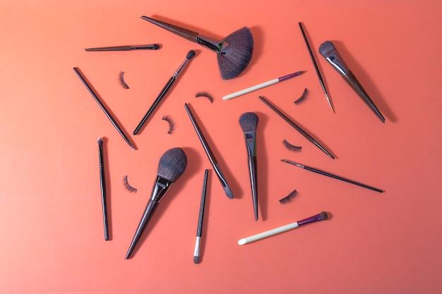 Oranje ondergrond waarop verschillende makeup kwasten en valse wimpers zitten voor professioneel gebruik Premium Foto