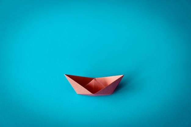 Oranje papieren boot op blauwe achtergrond met kopie ruimte, leren en onderwijs concept Premium Foto
