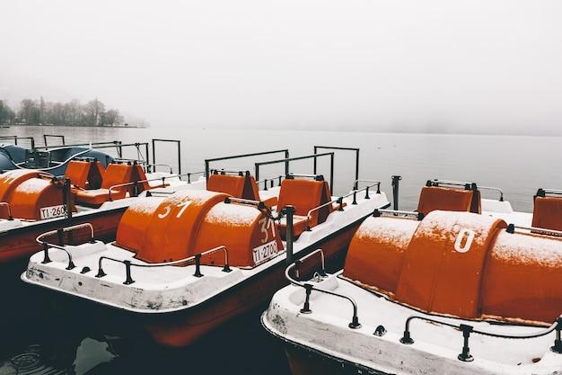 Oranje peddelboten bij de pier op een kalm meer vastgelegd op een mistige winterdag Gratis Foto