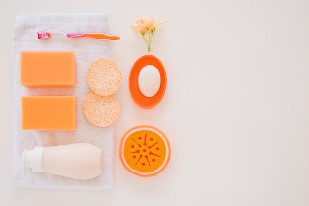 Oranje persoonlijke verzorgingsproducten op witte handdoek Gratis Foto