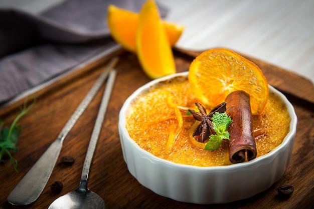 Oranje room brulee dessert in witte kom met kaneel en munt op houten achtergrond Premium Foto