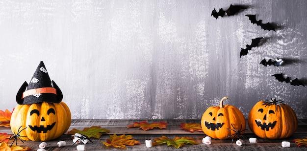 Oranje spookpompoenen met heksenhoeden en vleermuizen op grijs houten bord Premium Foto