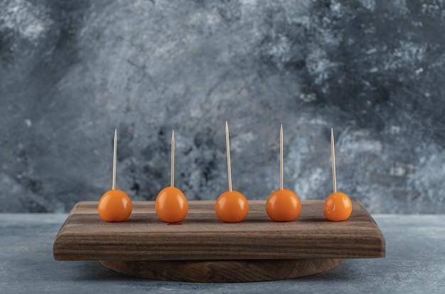Oranje tomaten met stokken op een houten bord. Gratis Foto