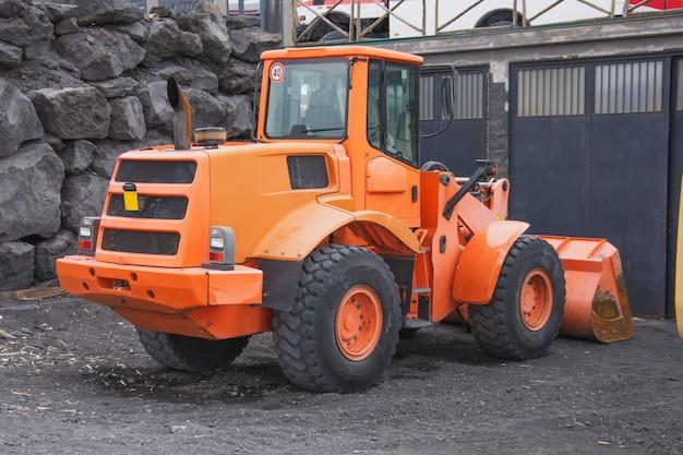 Oranje tractor met een emmer vooraan geparkeerd in de bergen. Premium Foto