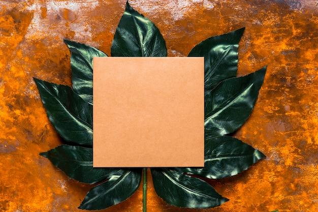 Oranje uitnodiging op groen blad Gratis Foto