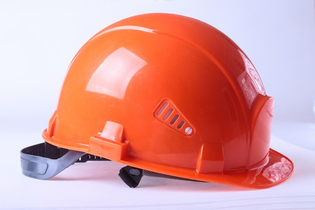 Oranje veiligheidshelm, die op witte achtergrond wordt geïsoleerd. Premium Foto