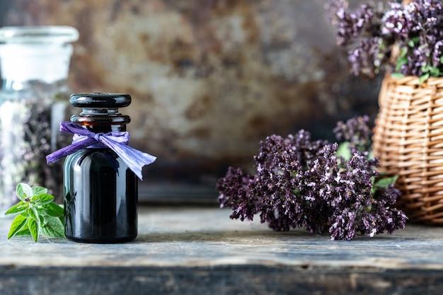 Oregano etherische olie in glazen fles op houten achtergrond. kopieer ruimte Gratis Foto