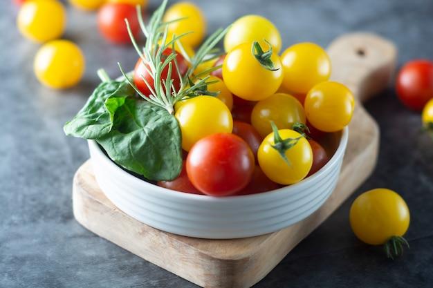 Organische gele en rode tomaten in plaat Premium Foto