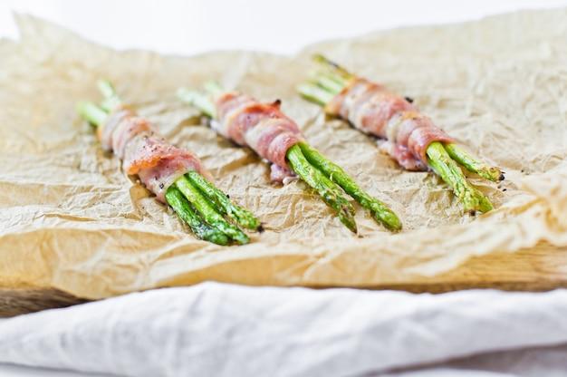 Organische groene miniasperge die in bacon op houten scherpe raad wordt verpakt. Premium Foto