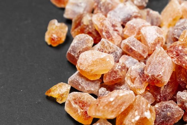 Organische kristallijne dichte omhooggaand van de bruine suikerrots op dark Premium Foto