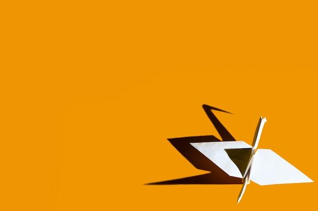 Origamikraan van papier op een felgele achtergrond met harde schaduw Premium Foto