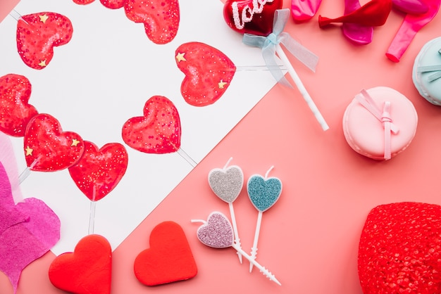 Ornament en geschilderde harten in de buurt van kaarsen en koekjes Gratis Foto